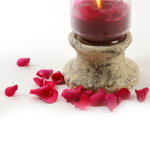 scatter cerise petals around a brightly coloured candle